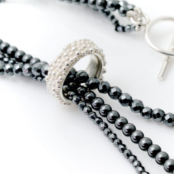 Haematite triple row bead necklace with silver beaded charm