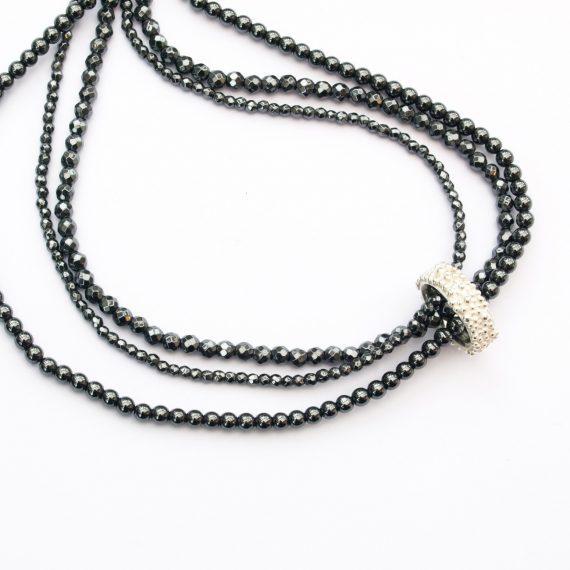 a triple row Haematite bead necklace with silver linking charm