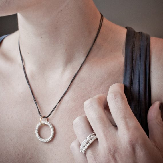 silver beaded circular necklace with gold plate and oxydised ball chain on model