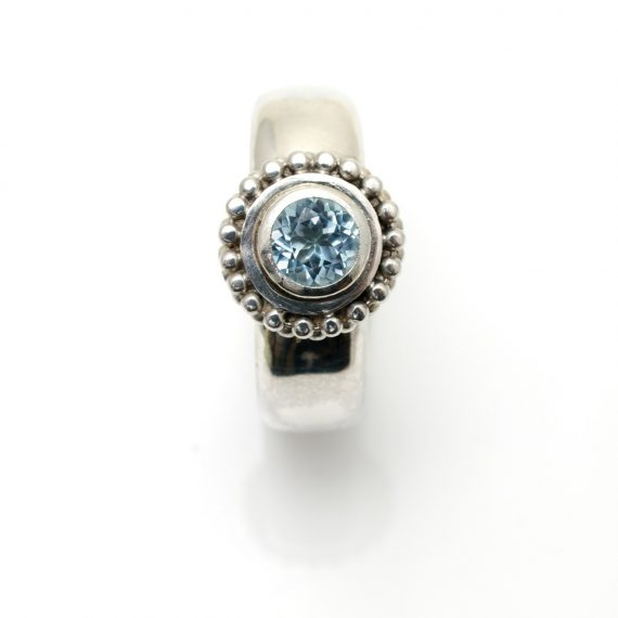 Silver decorative beaded ring with pale blue topaz