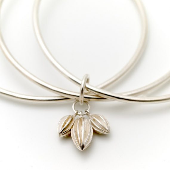 Triple silver bangle with seed pod charms