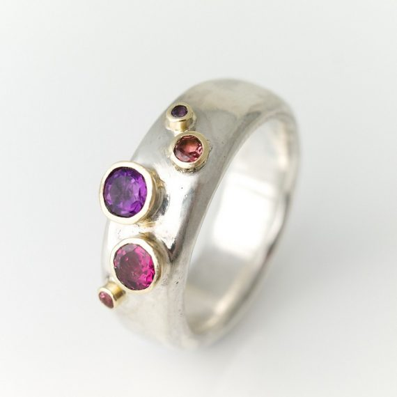 Wide silver ring with red and pink stones