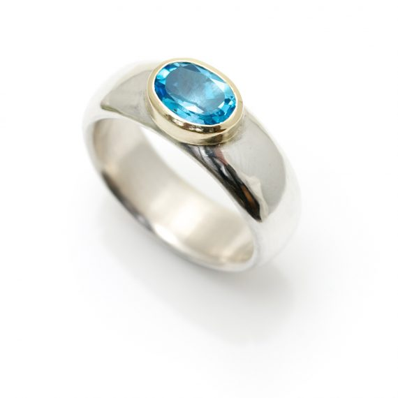 Wide silver ring with a Swiss Blue Topaz set in 18ct gold