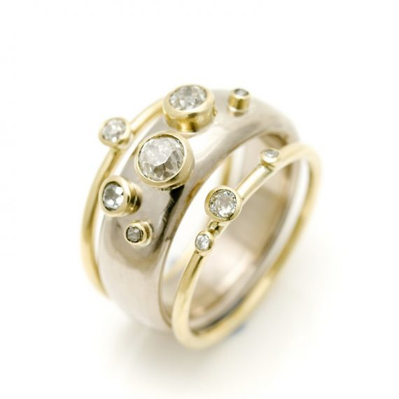 18ct white and yellow gold wide ring with narrow rings and scattered diamonds