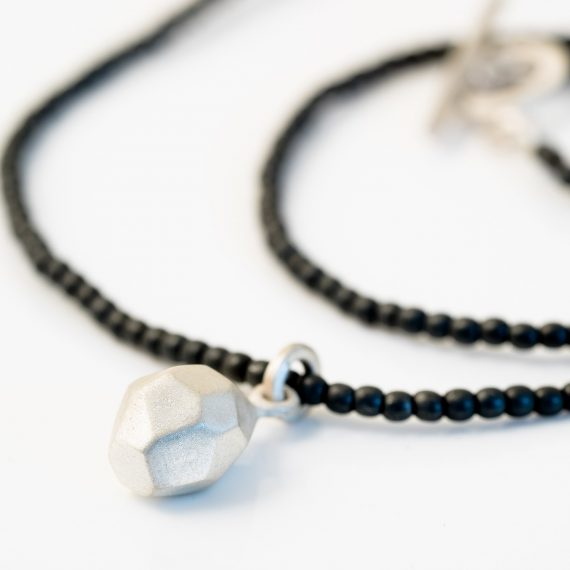 haematite bead necklace with silver geometric charm