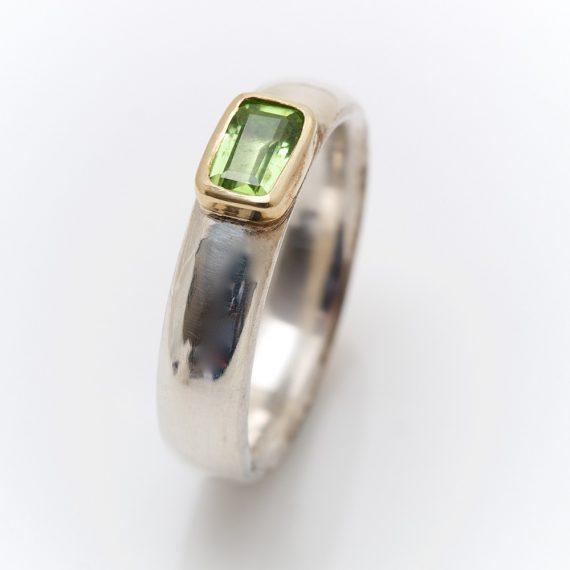 narrow chunky silver ring with rectangular peridot set in 18ct yellow gold